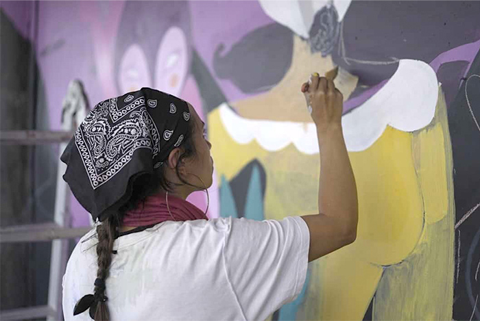 Mujer pintando mural en Centro Arte Alameda